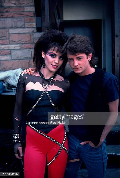 Portrait of American musician and actress Joan Jett and Canadian actor Michael J Fox as they pose outside the Thirsty Whale bar during filming of the...