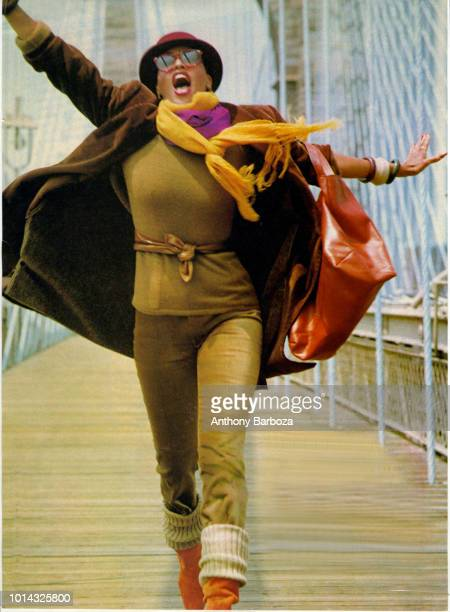 Portrait of American musician and actress Phyllis Hyman dressed in a scarf hat and winter coat as she walks arms stretched out across a bridge New...