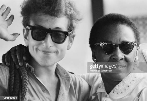 Portrait of American musician Bob Dylan with an unidentified woman as he smiles and waves during the Newport Folk Festival Newport Rhode Island July...