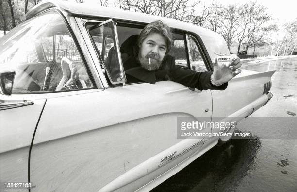 Portrait of American musician Bob Seger as leans out of the window of a car in Central Park New York New York December 13 1982 He holds a cigarette...