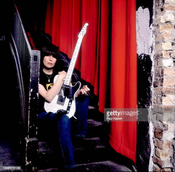 Portrait of American musician Chrissie Hynde, of the group Pretenders as she poses with her guitar, backstage at the Riviera Theater, Chicago,...