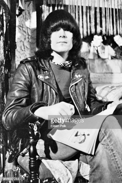 Portrait of American musician Dee Dee Ramone of the punk group Ramones a cigarette in one hand and an open magazine on his lap as he sits in the...