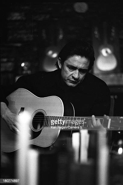 Portrait of American musician Johnny Cash as he plays an acoustic guitar 1970s