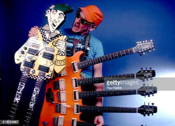 Portrait of American musician Rick Nielsen of the band Cheap Trick as he poses with two of his guitars at the Poplar Creek Music Theater Chicago...