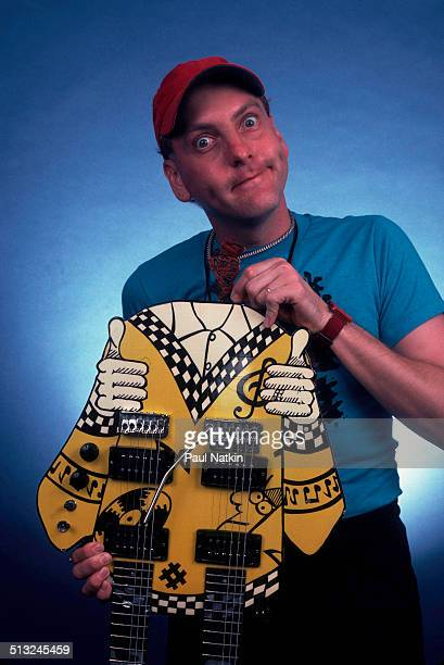 Portrait of American musician Rick Nielsen of the band Cheap Trick as he poses with one of his guitars at the Poplar Creek Music Theater Chicago...