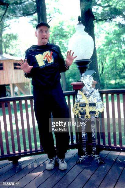 Portrait of American musician Rick Nielsen of the band Cheap Trick as he poses with one of his guitars on the porch of his home Rockford Illinois...
