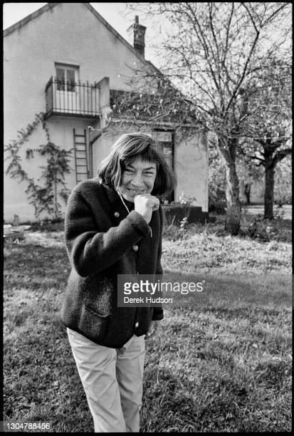 Portrait of American novelist and short story writer Patricia Highsmith as she smiles in the garden of her home, in the village of...