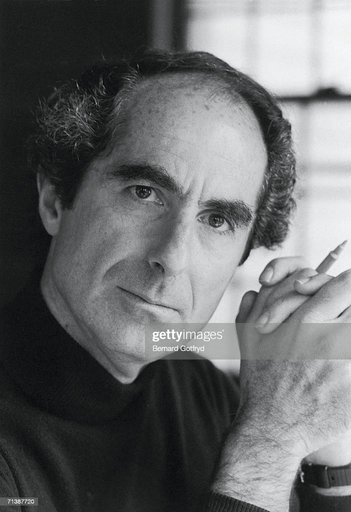 Portrait of American novelist Philip Roth as he sits with his hands clasped around a pen, 1983.