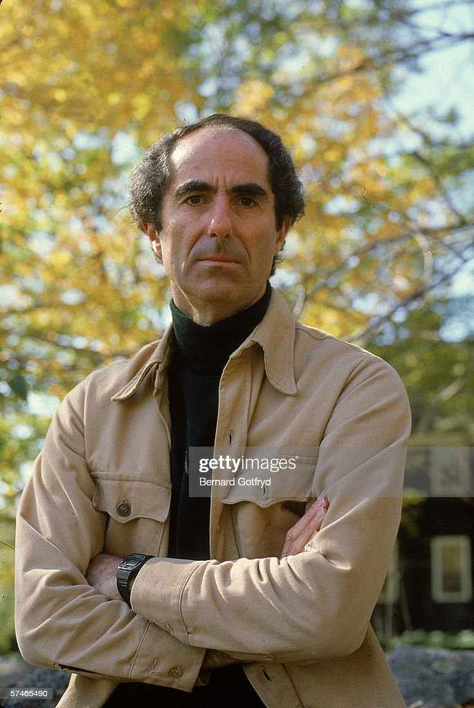 Portrait of American novelist Philip Roth, dressed in a turtleneck and jacket, who stands outdoors with his arms crossed, probably 1980s.