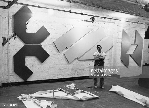 Portrait of American painter David Novros as he poses arms crossed with his work in his loft studio New York New York November 20 1965