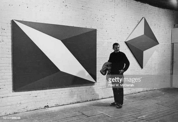 Portrait of American painter Dean Fleming as he poses with his work in his downtown loft studio New York New York November 14 1965