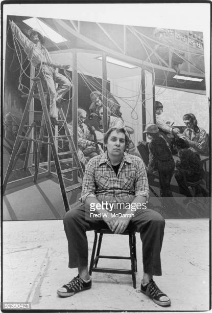 Portrait of American painter Jack Beal as he sits in a chair in front of one of his mural paintings entitiled '20th Century Technology' December 29...