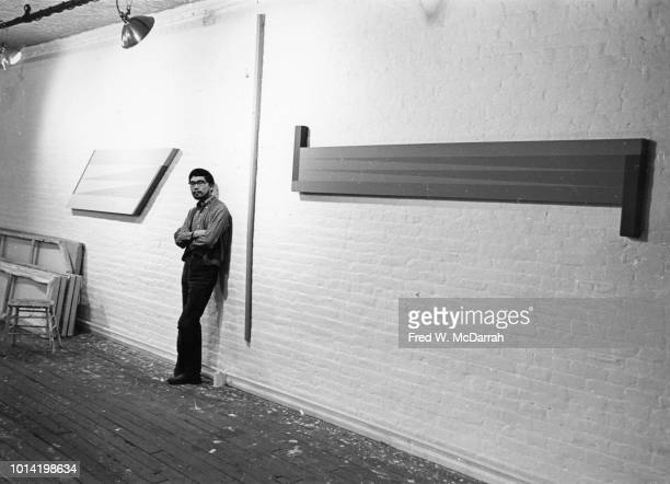 Portrait of American painter Leo Valledor as he leans against a brick wall between several piece of his work in his studio New York New York November...