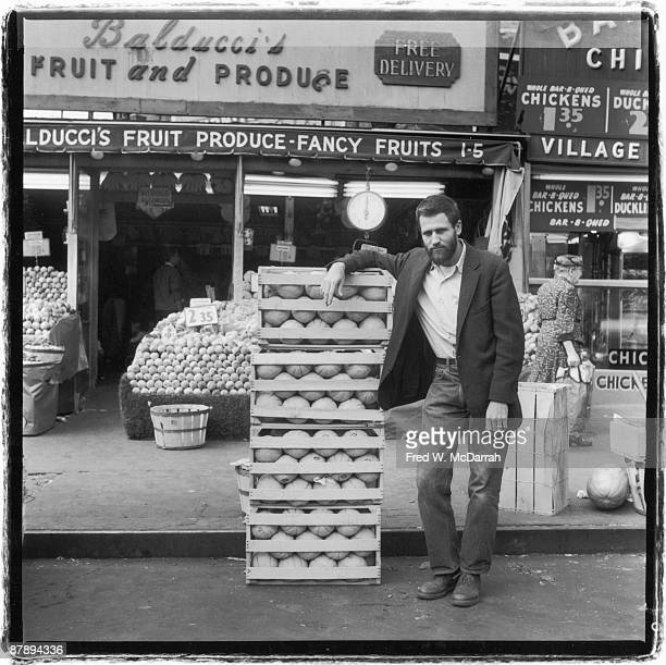 Portrait of American performance artist Allan Kaprow as he leans on a stack of melon crates outside of Balducci's market New York New York September...