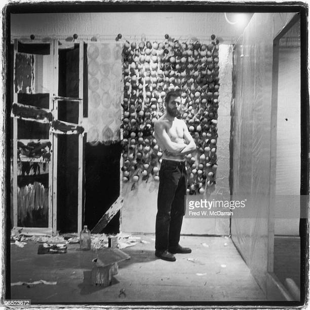 Portrait of American performance artist Allan Kaprow as he poses shirtless and arms crossed in front of one of his installations at the Ruben Gallery...