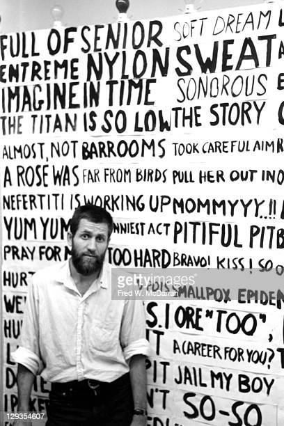 Portrait of American performance artist Allan Kaprow as he poses in front of a portion of his 'Words' environment in the Smolin Gallery New York New...