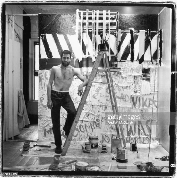 Portrait of American performance artist Allan Kaprow as he stands with on foot on a ladder as he sets up an exhibition at the Ruben Gallery New York...