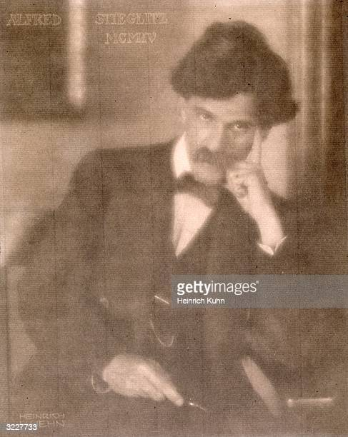 Portrait of American photographer Alfred Stieglitz sitting and holding his finger up to his temple taken by Germanborn Austrian photographer Heinrich...