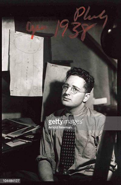 Portrait of American photographer Arnold Newman as he sits a table above which hang a series of childliek drawings 1938