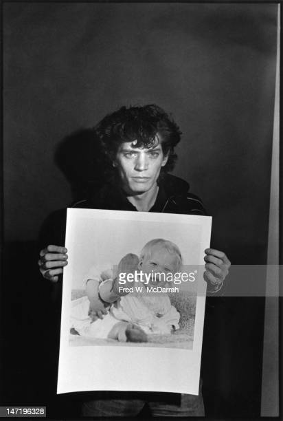 Portrait of American photographer as he poses with one of his photos in his loft studio New York New York December 22 1979