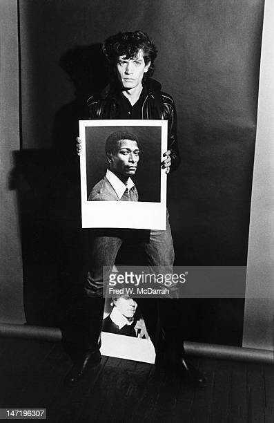Portrait of American photographer as he poses with several of his photos in his loft studio New York New York December 22 1979