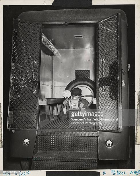 Portrait of American photographer Weegee as he poses with his camera lying on the floor in the back of a police wagon late 1930s Photo by Weegee...