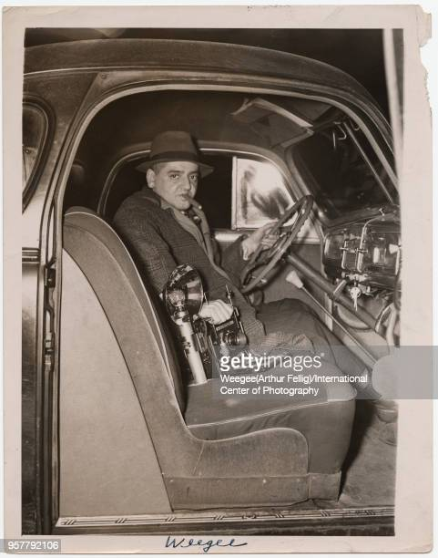 Portrait of American photographer Weegee as he sits behind the steering wheel of a car, circa 1940.