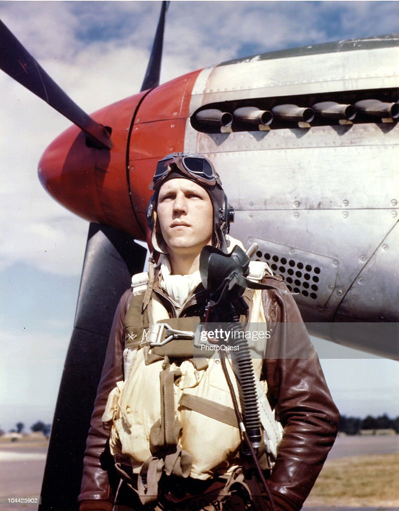Portrait of American pilot Lieutenant Robert J. Cooper as he poses next to a North American Aviation P-51 Mustang fighter plane at a base in England, 1944.