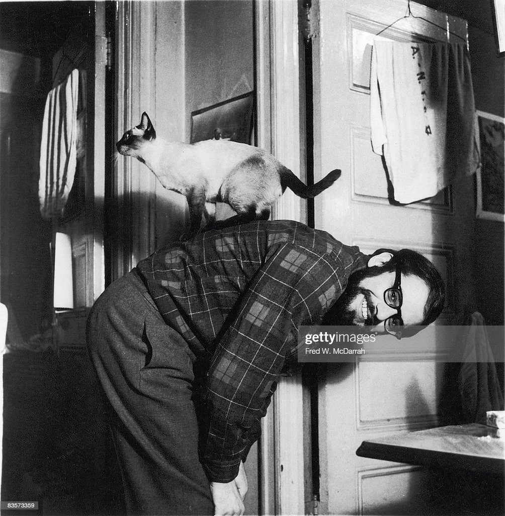 Portrait of American poet Allen Ginsberg (1926 - 1997) in his apartment (170 East 2nd Street) as he poses, bent at the waist, with his pet Siamese cat balanced on his back, New York, New York, Januray 9, 1960.