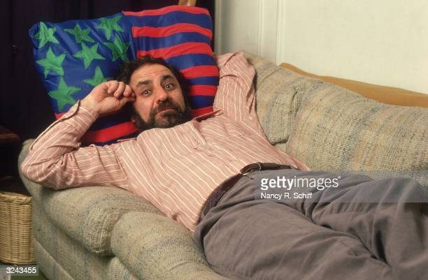 Portrait of American political activist Abbie Hoffman laying on a couch and resting his head on a pillow of the US flag