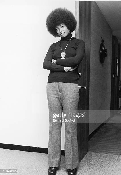 Portrait of American political activist and scholar Angela Davies as she leans against an open door her arms crossed in front of her New York New...
