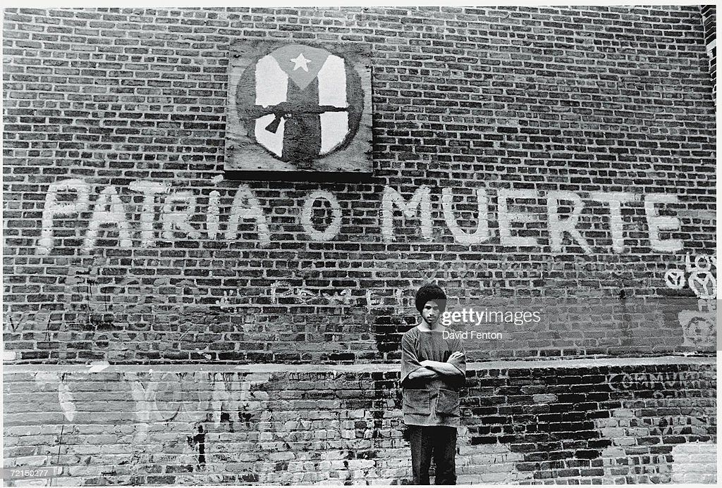 Portrait of American political and social activist Felipe Luciano and members of the Young Lords Organization (of which Luciano was a co-founder) as he stands with his arms crossed in front of a brick wall in Newark, New Jersey, July 23, 1970. The Young Lords sought promote Hispanic nationalism, self-determination, and education, and to improve social services in Puerto Rican neighborhoods. The graffiti on the wall behind him reads 'Patria o Muerte' ('My Country or Death') under a logo of a Puerto Rican flag and an assualt rifle.