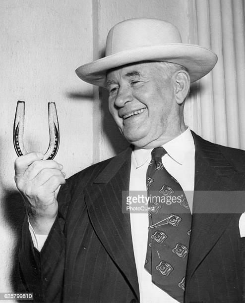 Portrait of American politician and Democratic vicepresidential candidate Senator Alben W Barkley as he holds up a Missouri mule shoe Washington DC...