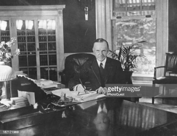 Portrait of American politician and US President Calvin Coolidge as he sits at his desk in the White House Washington DC August 15 1923