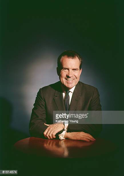 Portrait of American politician and US President Richard Nixon as he smiles and sits at a table 1960s