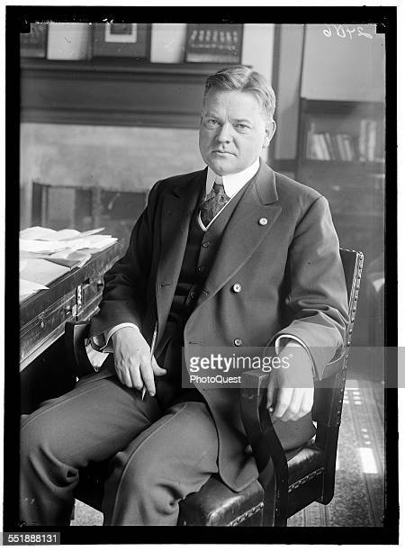 Portrait of American politician Herbert Hoover as he sits at a desk during his tenure as head of the US Food Administration 1917