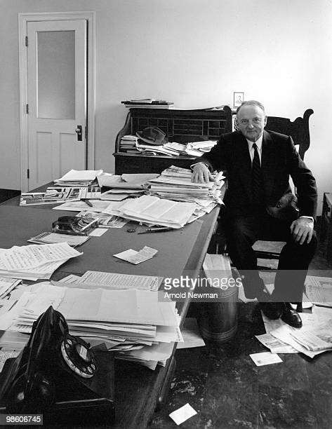 Portrait of American politician Senator Harry F Byrd as he sits at a desk crowded with papers a number of which have fallen to the floor about his...