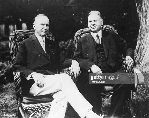 Portrait of American polticians US President Calvin Coolidge and his successor Herbert Hoover as they sit under a tree in wicker chairs as the Summer...