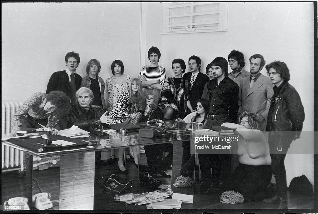 Portrait of American pop artist Andy Warhol (1928 - 1987) (seated, second left) and others assembled for a photo shoot with Cecil Beaton (not pictured) at Warhol's studio, the Factory (near Union Square), New York, New York, April 24, 1969. Pictured are, from left, Jay Johnson, Paul Morrissey, Andy Warhol, Eric Emerson, unidentified, Ingrid Superstar, Candy Darling, unidentified, Ultra Violet, Fred Hughes, unidentified, unidentified, unidentified, Cory Tippin, Sam Green, Gerard Malanga, and Brigid Polk.