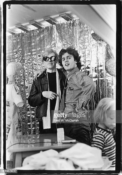 Portrait of American pop artist Andy Warhol and poet Gerard Malanga as they pose together in front of a mylar curtain in the Abraham Straus...