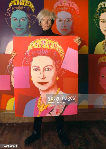 Portrait of American Pop artist Andy Warhol as he holds a silkscreen print of British monarch Queen Elizabeth II in his studio, the Factory, New...