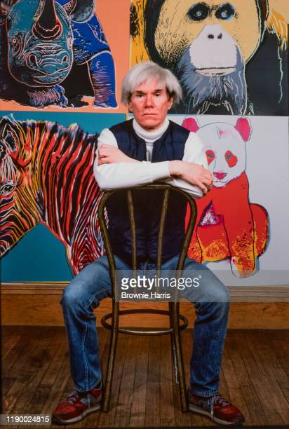 Portrait of American Pop artist Andy Warhol as he sits backwards on a chair in his Union Square studio, the Factory, , New York, New York, 1982.