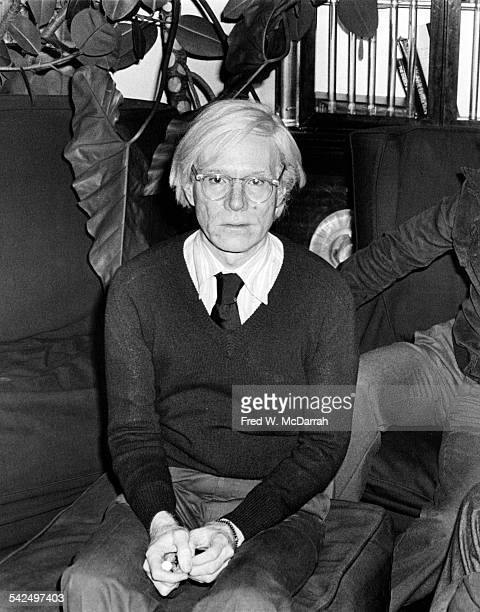 Portrait of American pop artist Andy Warhol as he sits on an ottoman in his loft New York New York October 4 1978
