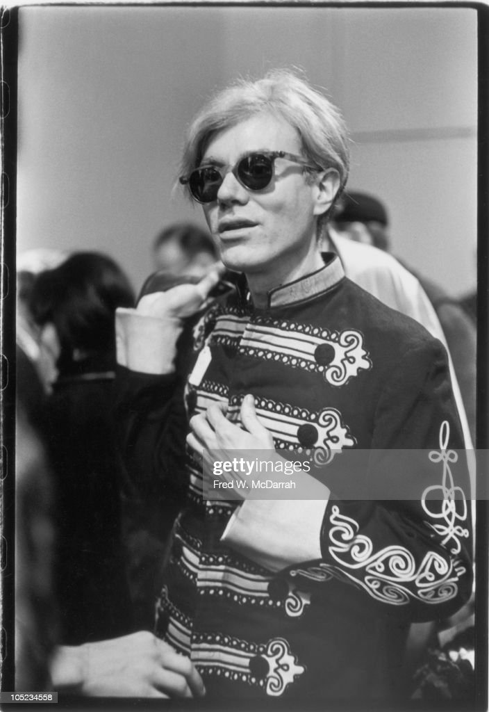 Portrait of American pop artist Andy Warhol (1928 - 1987) as he tries on a marching band uniform in a used clothing store (located on St. Mark's), New York, New York, December 9, 1966.