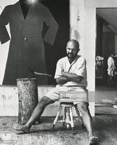 Portrait Of American Pop artist Jim Dine as he sits on a stool, East Hampton, New York, 1964. Visible in the background is one of his paintings.