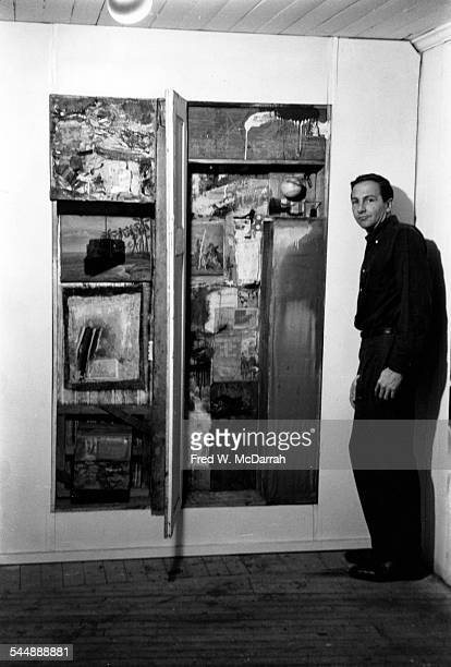 Portrait of American Pop artist Robert Rauschenberg as he poses beside an unidentified work on the wall of his Front Street loft studio New York New...