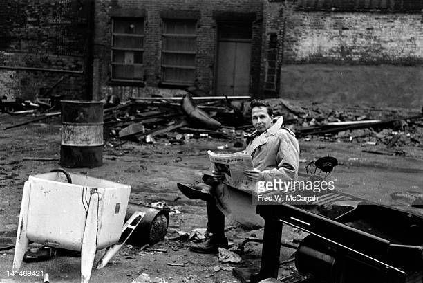 Portrait of American Pop artist Robert Rauschenberg as he reads a newspaper in a vacant lot near his studio New York New York January 15 1961