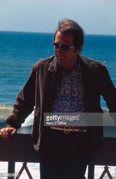 Portrait of American popular singer Andy Williams as he leans against a railing by the sea 1971