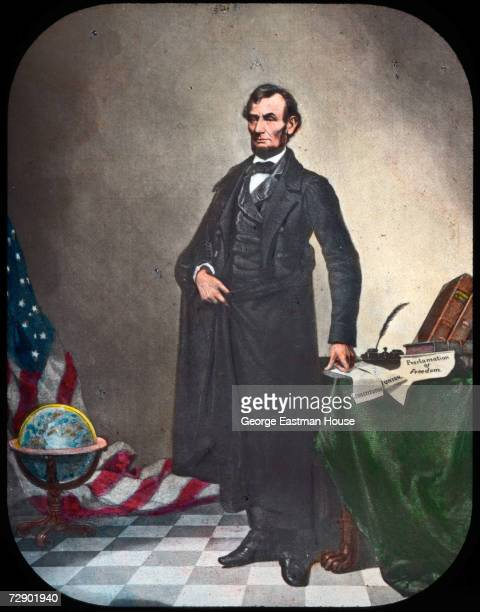 Portrait of American President Abraham Lincoln as he stands next to a table containing several documents labelled 'Constitution' 'Union' and...