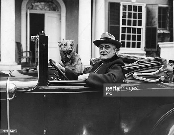 Portrait of American President Franklin Delano Roosevelt as he sits behind the wheel of his car outside of his home in Hyde Park New York mid 1930s